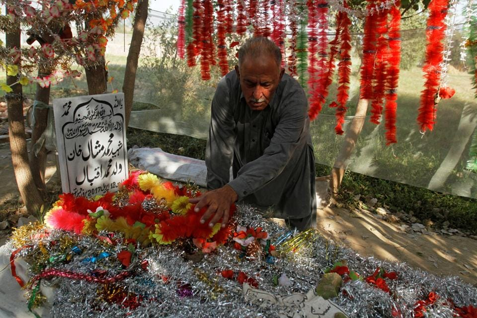 Iqbal Khan puts decorations on his son's grave in a family orchard in Swabi, Pakistan October 24, 2017. Picture taken October 24, 2017. REUTERS/Fayaz Aziz
