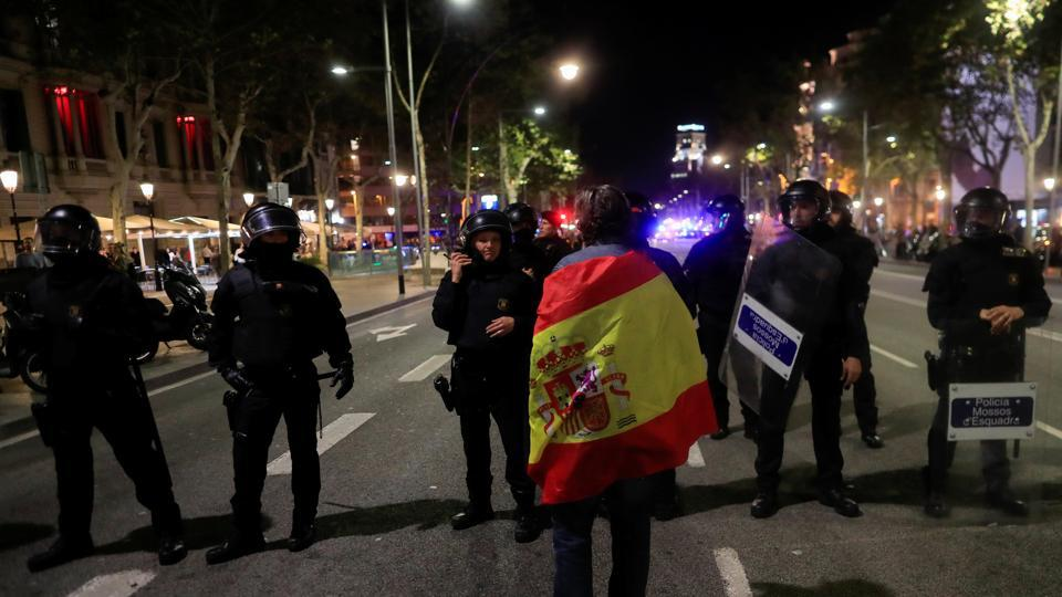 A pro unity demonstrator stands in front of Catalan Regional Police officers during a protest after the Catalan regional parliament declared independence from Spain in Barcelona, Spain, October 27, 2017.