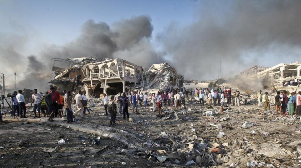 In this October 14 file photo, Somalis gather and search for survivors by destroyed buildings at the scene of a huge explosion in the capital Mogadishu, Somalia.
