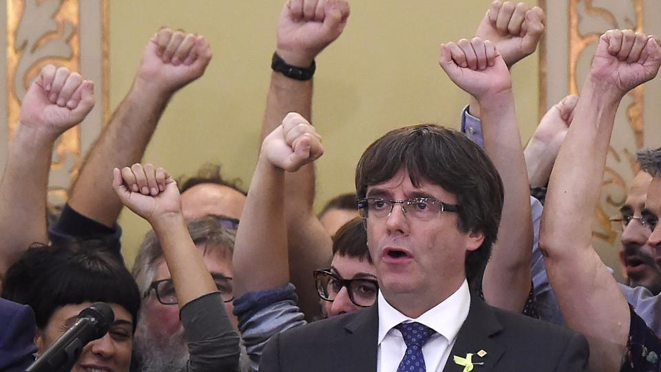 Catalan president Carles Puigdemont sings the anthem 'Els Segadors' after a session of the Catalan parliament in Barcelona on Friday. Puigdemont sought to widen support for independence, always by peaceful means, inspired by Mahatma Gandhi.