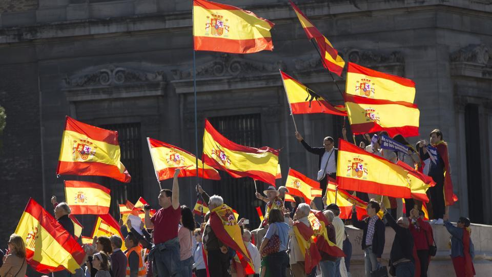 People wave Spanish flags during a mass protest over Catalonia's declaration of independence in Madrid on Saturday.