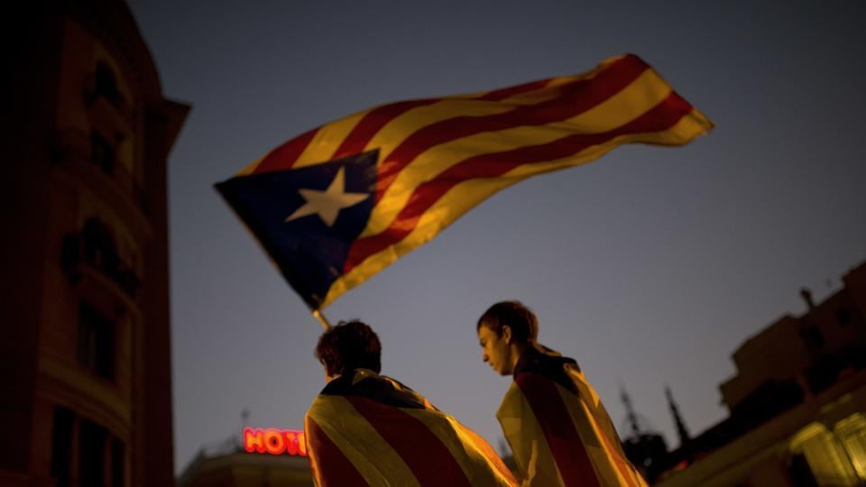 Pro-independence supporters carry an 'Estelada' or independence flag in downtown Barcelona.