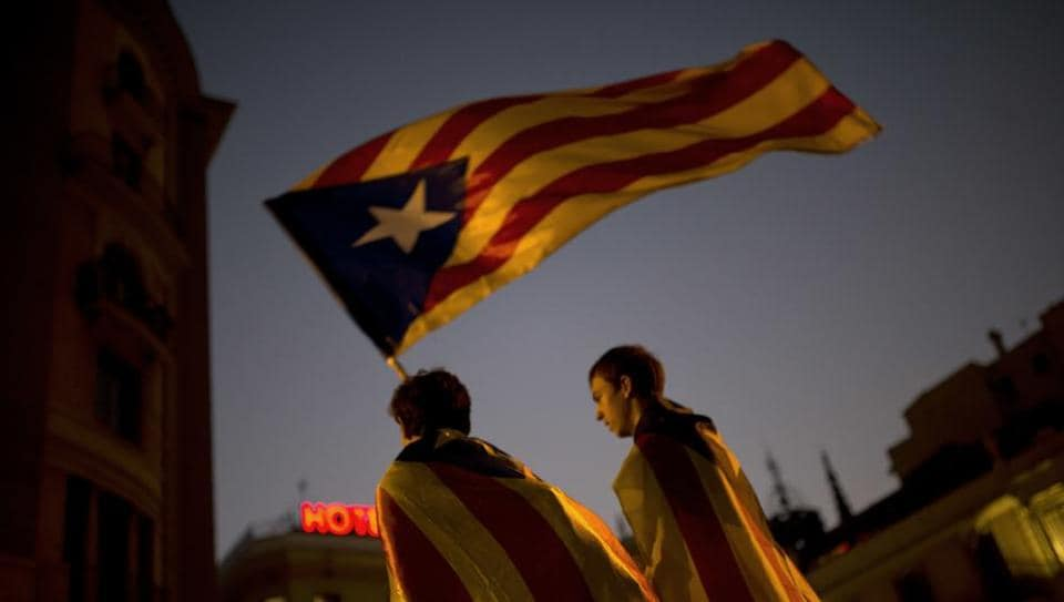 Pro-independence supporters carry an 'Estelada' or independence flag in downtown Barcelona Friday, Oct. 27, 2017.