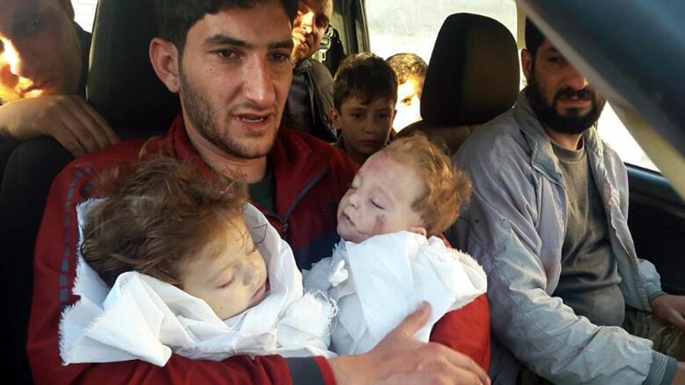 In this April 4, 2017 file photo, Abdel Hameed Alyousef, 29, holds his twin babies who were killed during a suspected chemical weapons attack, in Khan Sheikhoun in the northern province of Idlib, Syria.