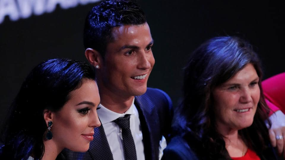 Real Madrid's Cristiano Ronaldo celebrates after winning The Best FIFA Men's Player Award with partner Georgina Rodriguez and mother Maria Dolores dos Santos Aveiro in London on October 23, 2017.