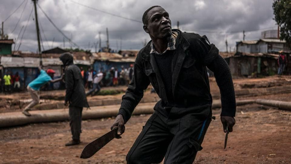 A protester brandishing a machete and a knife prepares to take cover from incoming tear gas canisters during clashes with police forces in Kibera, Nairobi, on October 26, 2017.  (Marco Longari / AFP)