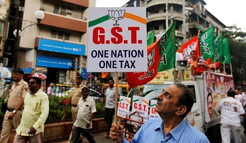 A supporter of the ruling Bharatiya Janata Party (BJP) holds a placard during a rally to support the implementation of the Goods and Services Tax (GST) in Mumbai.