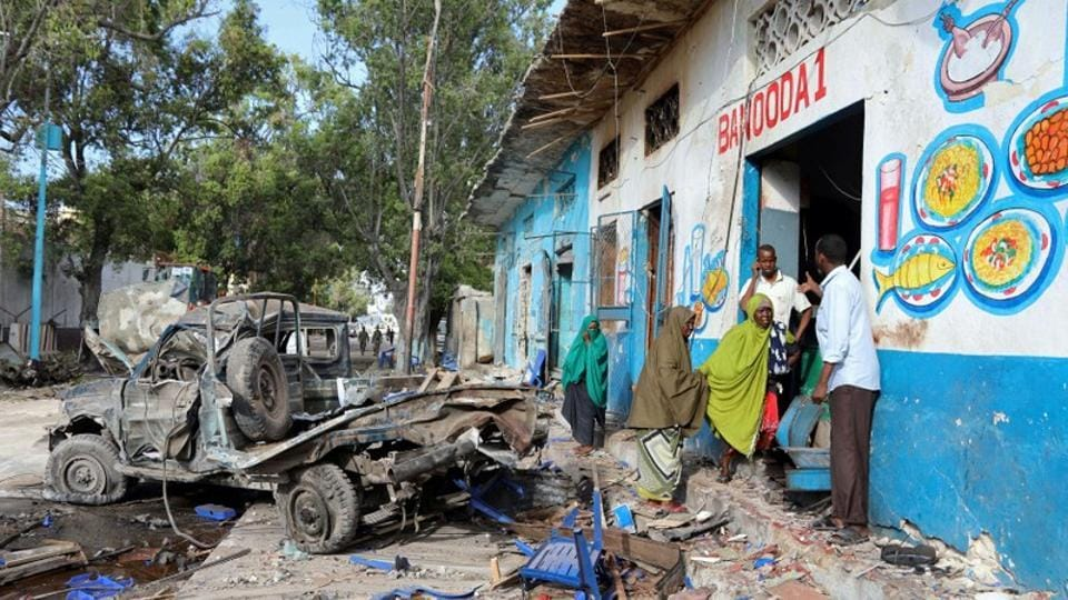 Residents gather at the scene of a suicide car bomb explosion, at the gate of Naso Hablod Two Hotel in Hamarweyne district of Mogadishu, Somalia.