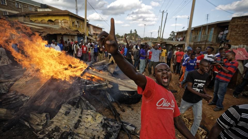 An opposition supporter yells in front of a burning barricade built from material looted from the property of a man of the Kikuyu tribe in the Nairobi's Kawangware slum. While the dynamics of 2017's political crisis are very different, the memory of the bloodshed a decade ago is never far away. (Ben Curtis / AP)