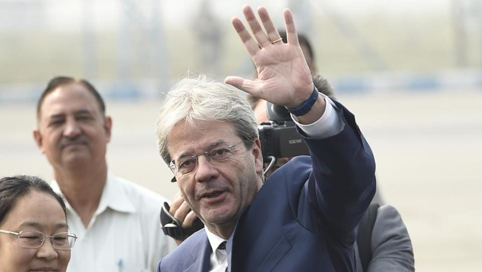 Italian Prime Minister Paolo Gentiloni waves after his arrival at Palam Air Force station in New Delhi Sunday.