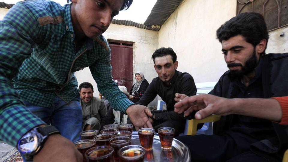 Tea was served to the groom and the guests during the wedding celebrations. Eighteen-year-old Ahmad (C) was dressed in a traditional brown robe for his wedding. (Delil souleiman / AFP)