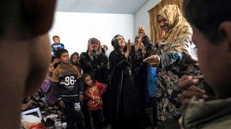Syrian women and children danced as they participated in celebrations. Female guests, forced under jihadist rule to wear all-enveloping black robes including gloves and face veils, took obvious delight in sporting patterned robes and bright red lipstick. Some covered their hair with matching patterned scarves, while others, including the bride, had their locks coiffed for the occasion. (Delil souleiman / AFP)