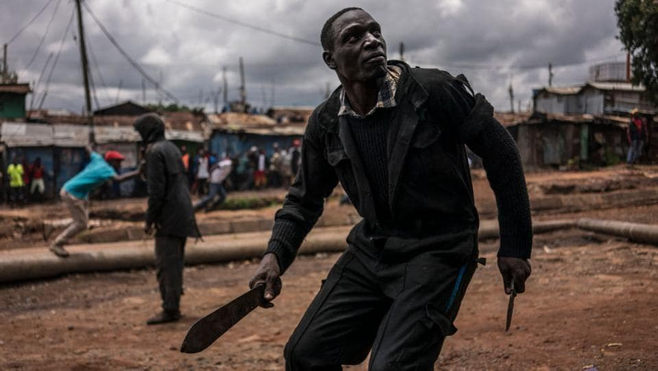 A protester brandishing a machete prepares to take cover during clashes with police forces in Kibera, Nairobi. Kenya's election board is expected Monday to decide whether to reschedule a vote in flashpoint opposition areas, where a boycott sparked violent protests, or to push ahead with declaring victory for President Uhuru Kenyatta. (Marco Longari / AFP)
