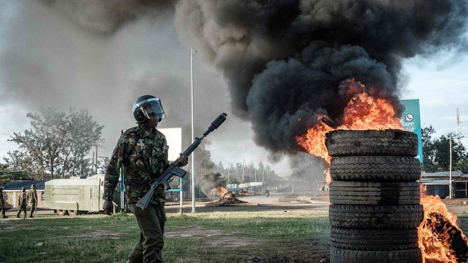 An anti-riot police officer walks by burning tires set alight by from supporters of Raila Odinga's National Super Alliance (NASA) at Kondele where a polling station was supposed to be setup for the repeat presidential election on October 26, 2017. Kenyans voted in an election that has polarised the nation and sparked concern about the future of east Africa's most stable democracy. Following Odinga's boycott, Kenyatta is guaranteed a crushing win. (Yasuyoshi Chiba / AFP)