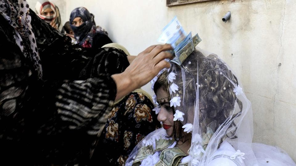 Guests showered the bride Heba (R) in cash during her wedding ceremony. 'Before IS, there was dabke, songs and the traditional rituals of the region at our marriages, but IS banned everything, there was not a single celebration,' a guest told AFP. (Delil souleiman / AFP)