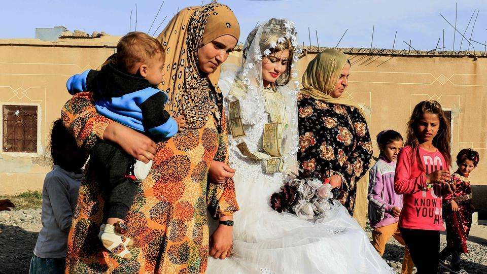 Syrian women escorted bride Heba as they participated in celebrations during her wedding. Heba entered the venue in a delicate veil edged with white flowers rested on her tightly curled hair, and a gold headpiece dangled over her eyebrows. Her hands were painted with henna as she fiddled nervously with a bouquet of artificial flowers. (Delil souleiman / AFP)