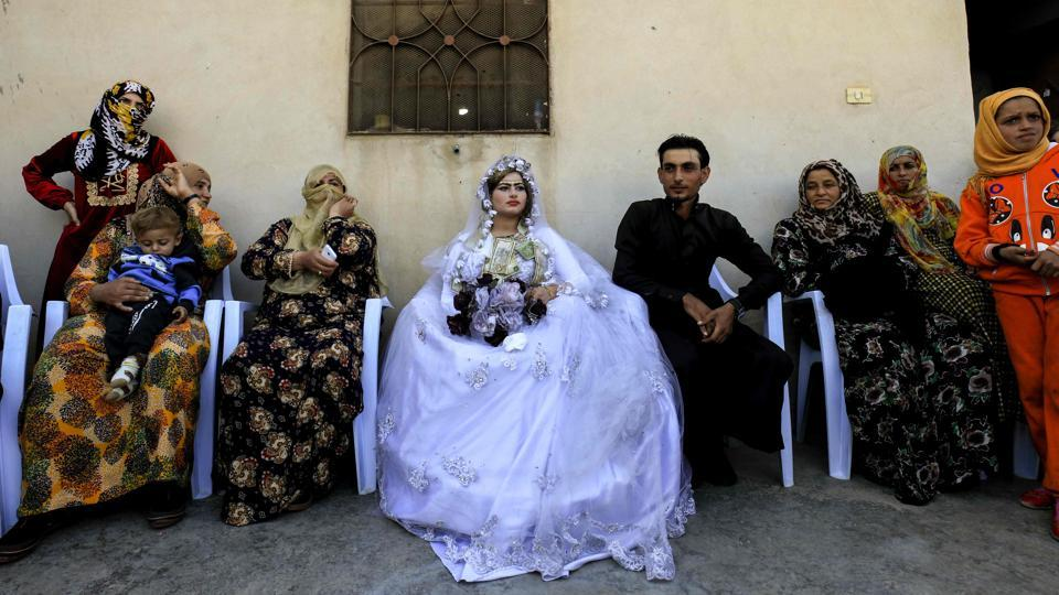 The groom Ahmed (Center-R) and bride Heba (Center-L) seated during their wedding. Residents told AFP that Ahmad and Heba's wedding, held on Friday in Raqqa's western neighbourhood of Jazra, was the first in the city since US-backed forces reclaimed it from ISIS. (Delil souleiman / AFP)