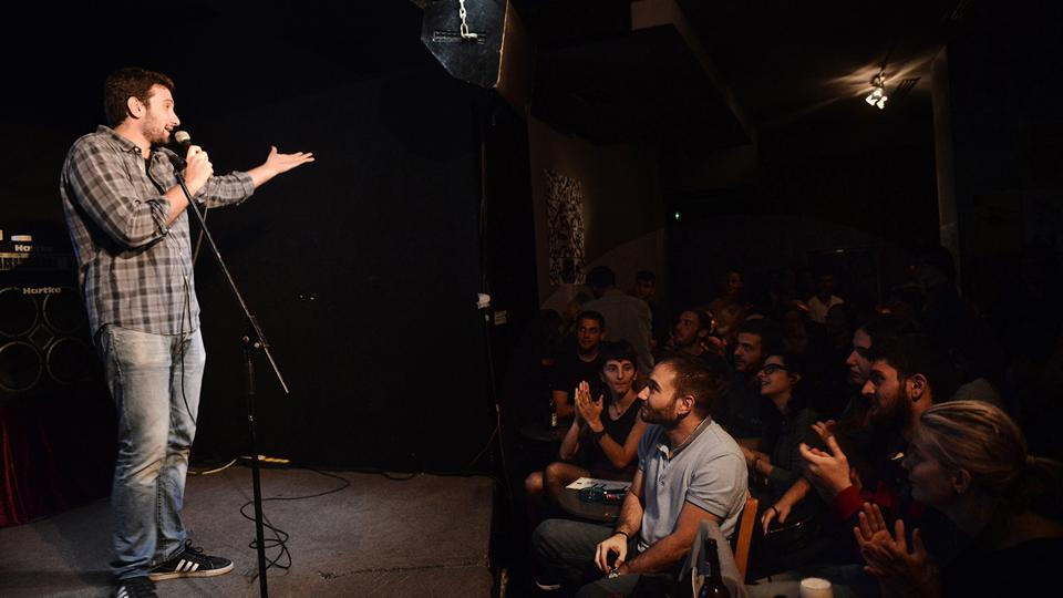 Comedian Andreas Paspatis performs during a stand-up comedy in a bar in Thessaloniki.