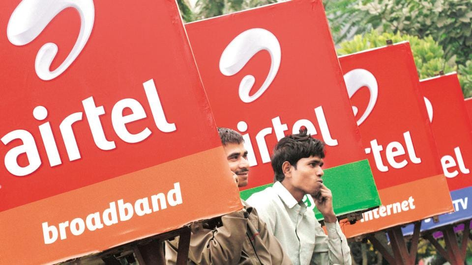 Men make phone calls as they sit on a railing with Bharti Airtel billboards installed on it, along a sidewalk in Kolkata.