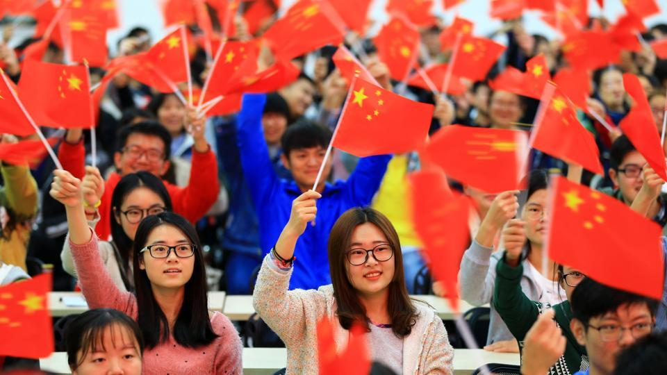 College students wave national flags in Huaibei in China's Anhui province. People may now face criminal penalties for disrespect of the national anthem.