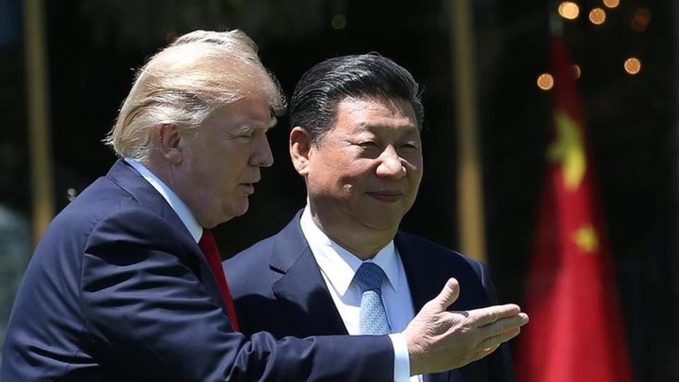 US President Donald Trump and China's President Xi Jinping walk along the front patio of the Mar-a-Lago estate after a bilateral meeting in Palm Beach, Florida, US.