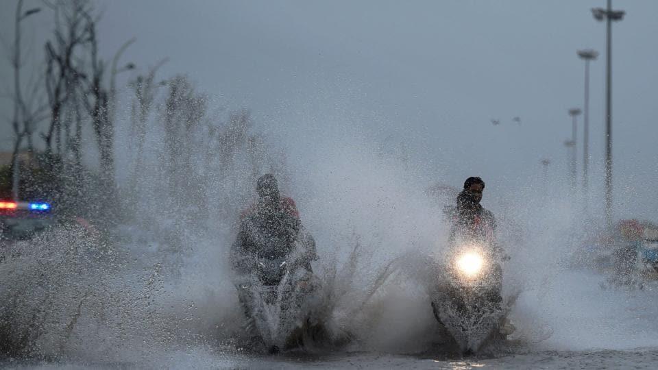 People ride their bikes through a waterlogged service road near Marina beach in Chennai on Monday.
