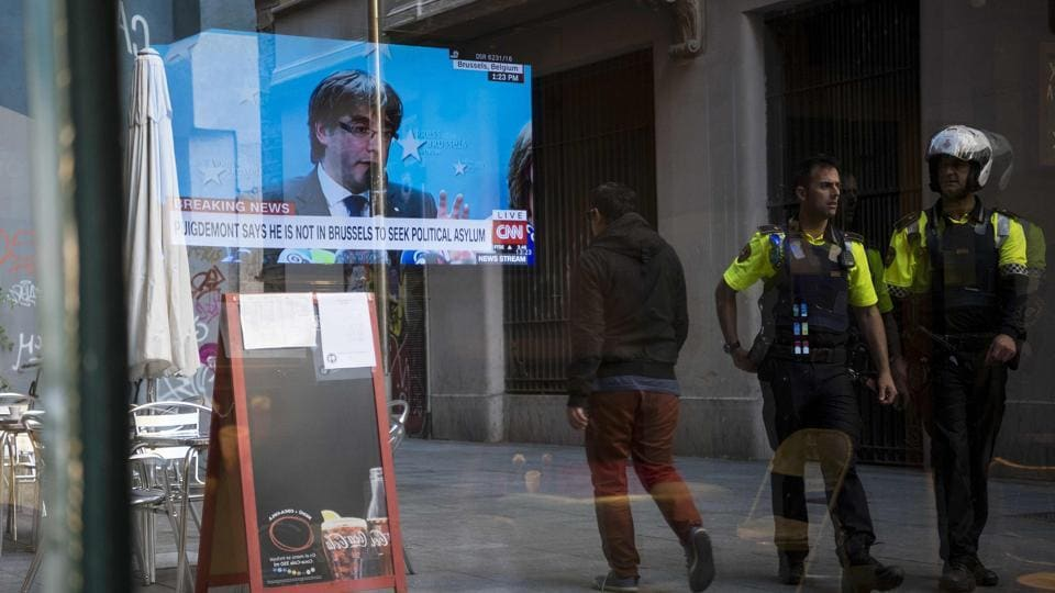 Two Catalan urban guard police officers walk past a bar in Barcelona showing a live broadcast of deposed Catalan leader Carles Puigdemont's news conference in Brussels on October 31.
