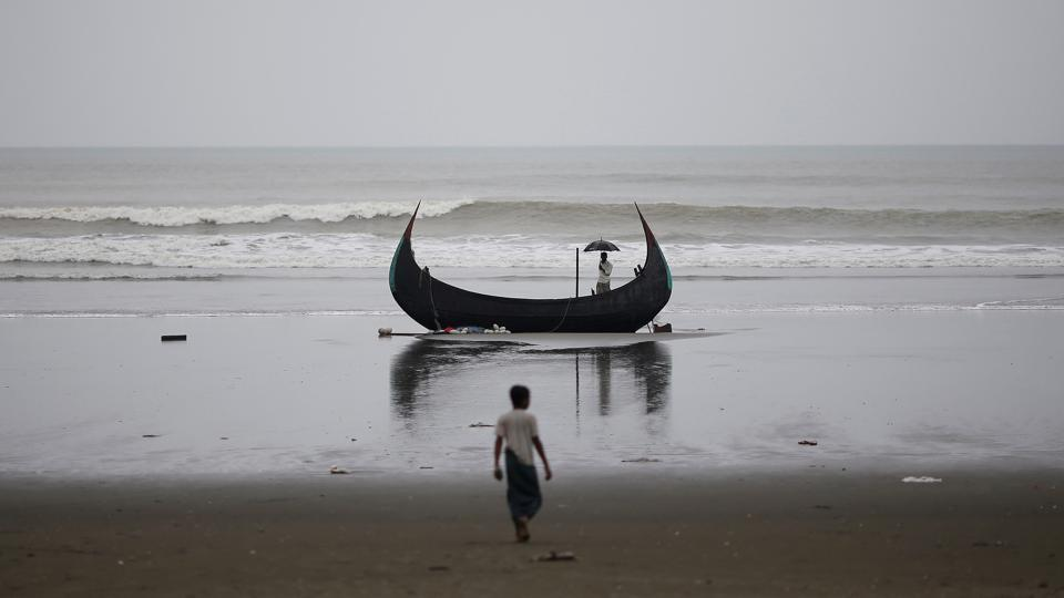 A man holds an umbrella as he stands on a boat, which capsized with a group of Rohingya refugees at Bailakhali near Cox's Bazar, Bangladesh, on Monday.