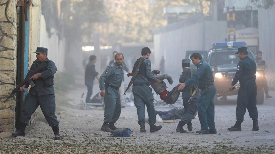 Afghan policemen carry an injurid after a blast in Kabul, Afghanistan October 31, 2017.