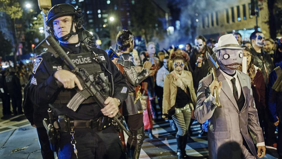 Heavily armed police guard as revelers march during the Greenwich Village Halloween Parade on October 31, 2017, in New York. The city's always surreal Halloween parade marched on Tuesday evening under the shadow of fear, hours after the truck attack killed several people on a busy city bike path, albeit under tight security and a large police presence. (Andres Kudacki / AP)