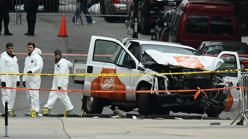 Investigators work around the wreckage of a Home Depot pickup truck a day after it was used in a terror attack in New York on November 1