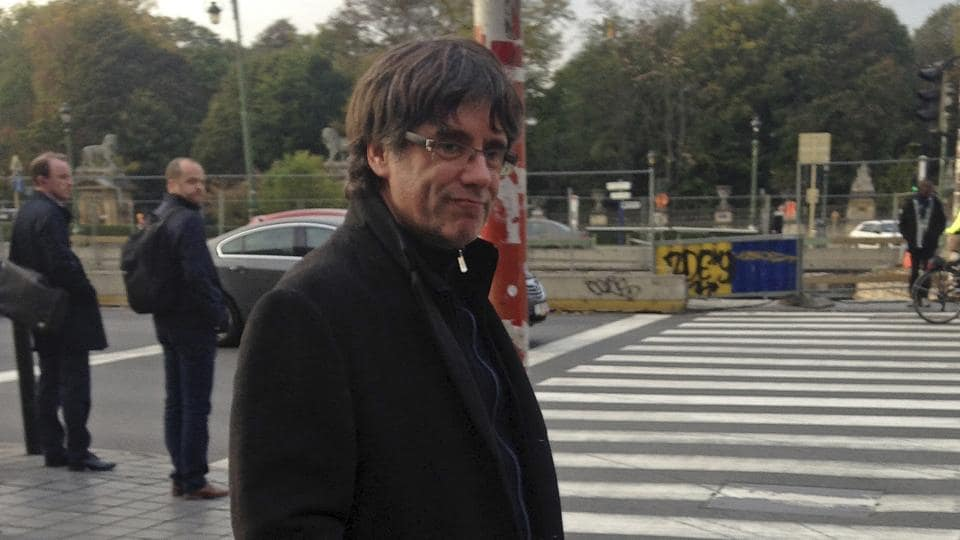 Ousted Catalan leader Carles Puigdemont walks along a street after giving a press conference in Brussels, Tuesday, Oct. 31, 2017.