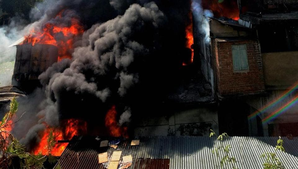 Smoke rises from a building where a major fire broke out, at Tokobari Satra in Guwahati on Wednesday.