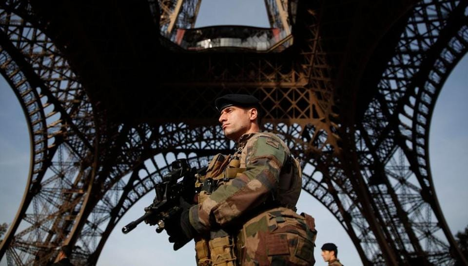A French soldier patrols in front of the Eiffel Tower on November 1, 2017 in Paris, as France officially ends the state of emergency.