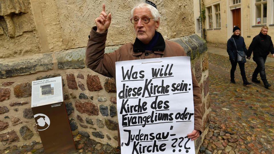A lone protester displays a placard reading 'What does this Church want to be: Gospel Church or 'Jew-Pig' Church???' as he protests against the so-called 'Judensau' (Jew-Pig) sculpture in Wittenberg. (John Macdougall / AFP)