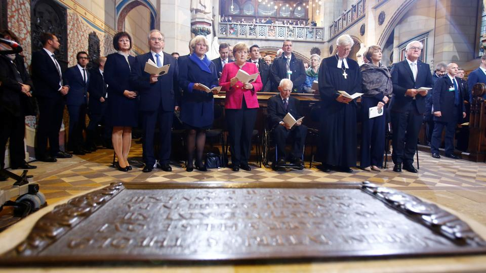 German President Frank-Walter Steinmeier (R) and Chancellor Angela Merkel (C) stand at the grave of Martin Luther during a celebratory mass in the All Saints' Church in Wittenberg on October 31, 2017. Merkel, herself the daughter of a Protestant pastor, said during a speech at the City Hall that 'Luther had spurred a movement that nothing can stop.' Adding, 'He laid the groundwork for a new understanding of Man and the eventual development of modern democracy. (Hannibal Hanschke / Pool /  AFP)