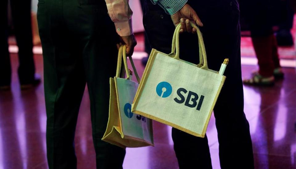 The State Bank of India (SBI) logo is seen on bags carried by people in Mumbai.