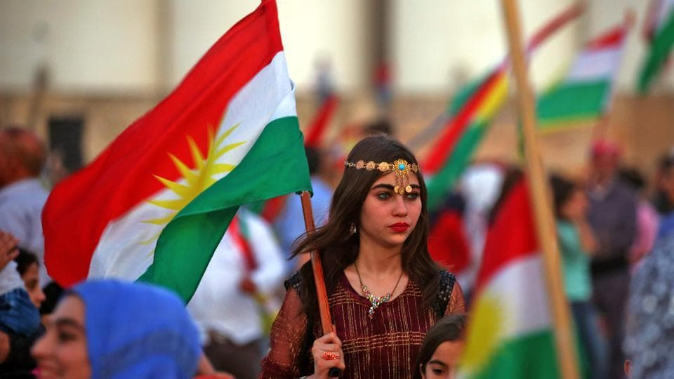 Syrian Kurds wave the Kurdish flag in celebration of the independence referendum in Iraq's autonomous northern Kurdish region, in the Syrian city of Qamishli on September 26, 2017. Thousands in the Kurdish region had cast votes on September 25 in a referendum which was billed as a first step towards independence from Baghdad, defying fears that the outcome could spark violence. (Delil Souleiman / AFP )