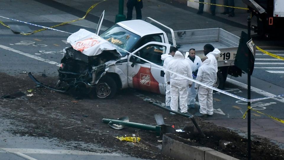 Investigators inspect the truck which plowed into a pedestrian and bike path in Lower Manhattan. The driver was shot in the abdomen by police after jumping out of the truck with what turned out to be paintball and pellet guns and shouting what witnesses said was 'Allahu Akbar' authorities said. The man underwent surgery and was in critical condition but was expected to survive. (Don Emmert / AFP)