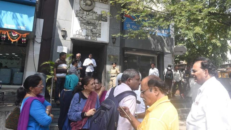 Investors gather outside the DSK offices on JM road this morning.