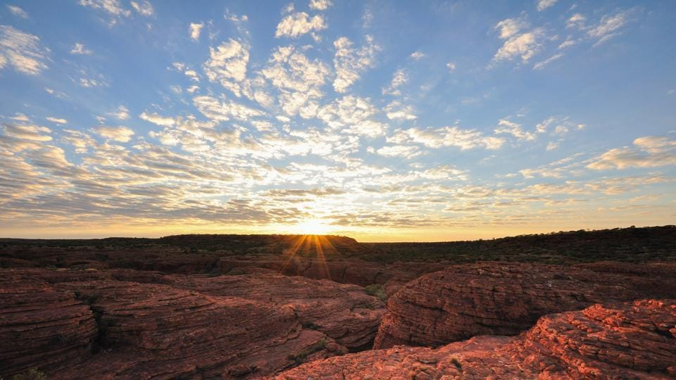 Scrambling up the symbol of the Outback, also known as Ayers Rock, is popular among many tourists.