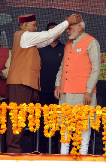 BJP's chief ministerial candidate Prem Kumar Dhumal presenting a Himachali cap to Prime Minister Narendra Modi. (SHYAMSHARMA/HT)