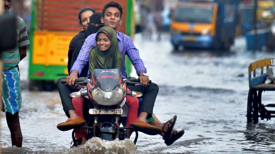 A motorcyclist wades through a flooded street in an inundated locality in Chennai. Traffic on most of the arterial roads came to a crawling halt as the roads were flooded with water of up to knee level in most areas. (PTI)