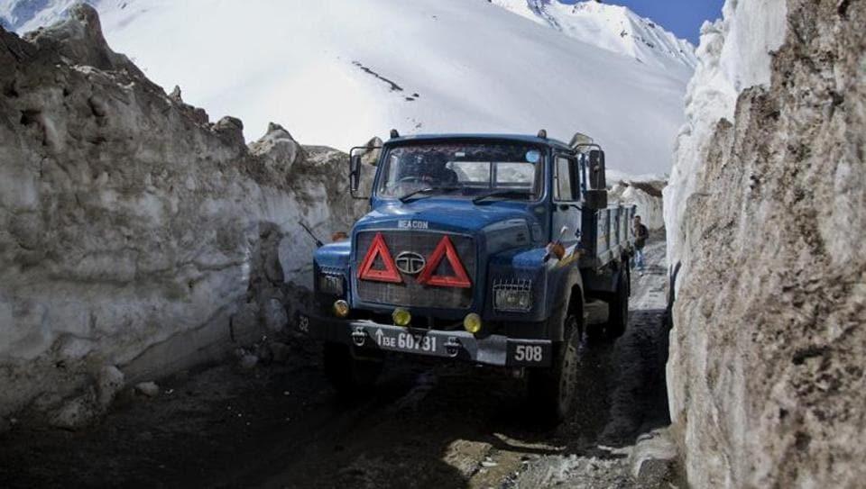A Border Road Organization truck drives past walls of snow on the Zojila Pass, about 110 kilometers north of Srinagar on April 30, 2016.