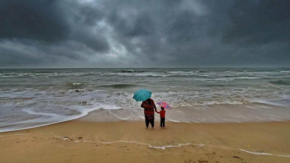 A woman stands with her son at Marina beach following heavy downpour due to the onset of Northeast monsoon in Chennai. More than 10,000 fishermen stayed in port Saturday as the sea remained very rough with waves rising to several feet  (PTI)