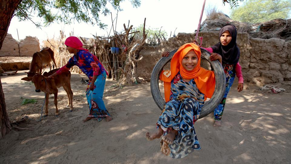 Saida strokes a calf as her sisters Amal (front), and Jalila play on a swing near their family's hut. Saida is able to help her father tend to a farmer's cattle in exchange for milk, with their income boosted by Ahmed making deliveries on his motorcycle and donations from humanitarian organizations. (Abduljabbar Zeyad / REUTERS)