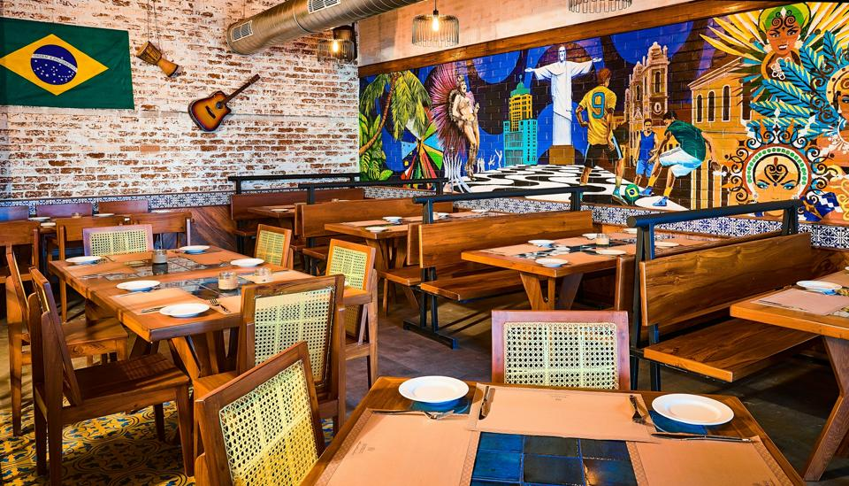 Boteco is bustling with detail — tiled tabletops, cane-backed chairs, a massive hand-painted mural (featuring football and Rio's Christ The Redeemer statue), a guitar strung on an exposed brick wall and glimmering blue glass windows.