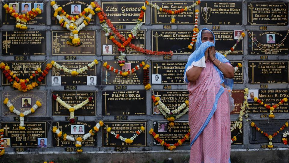 A woman cries after praying beside a columbarium at a cemetery during the observance of All Souls Day in Mumbai on November 2, 2017.  (Danish Siddiqui / REUTERS)