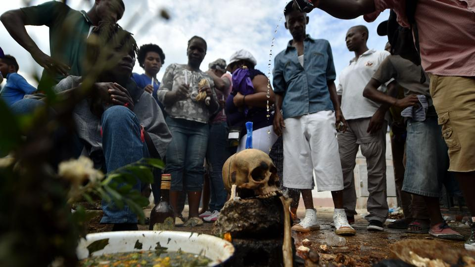 Voodoo devotees offer candles, alcohol and food to Baron Samdi, known for his fondness for tobacco and rum, his debauchery and obscenity during Fete Gede celebrations. The Day of the Dead is celebrated on the first two days of November during All Saints and All Souls Day.  (Hector Retamal / AFP)