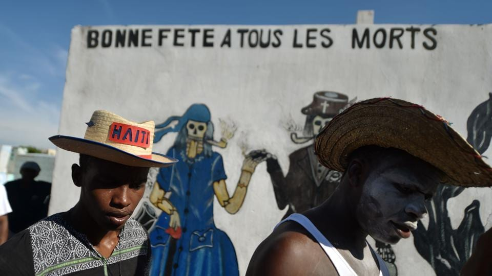 Voodoo devotees in costume take part in Fete Gede celebrations in the National Cemetery, in Port-au-Prince. A mural in the background features voodoo spirits and reads 'Happy Birthday to all the dead'. (Hector Retamal / AFP)